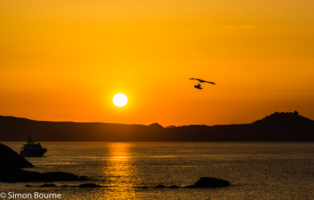 Simon Bourne, photography, photographer, north London, portfolio, image, landscape, seascape, sea, island, Mediterranean, Sardinia, Italy, Nikon, sunset, dusk, sun rays, Icarus, sea plane, boat plane, bay, coast, rocks, orange sky, ship, boat