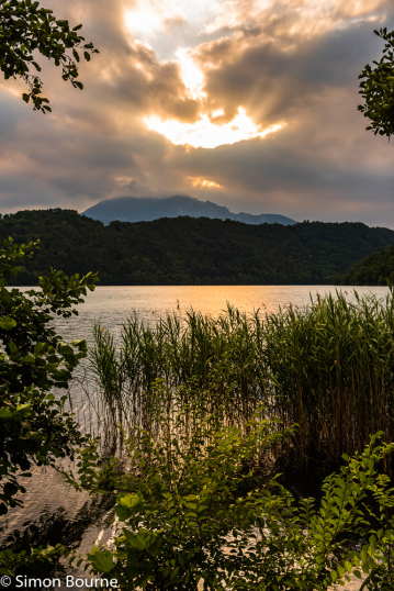 Simon Bourne, photography, photographer, north London, portfolio, image, landscape, Italy, Nikon, Levico Terme, Lago di Levico, Trentino, lake, water, mountain, trees, sunset, dusk, alpine, Dolomites, storm clouds, reeds, bushes, crepuscular rays, stormy