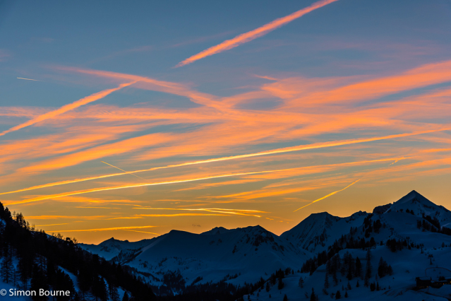 Simon Bourne, photography, photographer, north London, portfolio, image, landscape, Austria, Nikon, Obertauern, alps, alpine, mountain, trees, orange sky, red skies, snow, sunset, vapour trails, planes, dusk, clouds, peaks, skiing, ski resort
