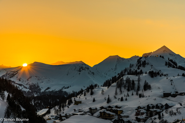 Simon Bourne, photography, photographer, north London, portfolio, image, landscape, Austria, Nikon, Obertauern, alps, alpine, mountain, trees, orange sky, snow, sunset, dusk, peaks, skiing, ski resort, starburst