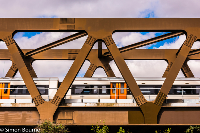 Simon Bourne, photography, photographer, north London, portfolio, image, bridge, structure, Nikon, GE19 Bridge, railway, Shoreditch, East London, early morning, spring, sun, blue skies, train, TfL Overground, East London Line, Benaim, steel girders, Warre