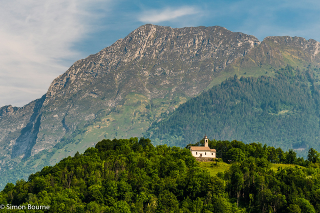 Simon Bourne, photography, photographer, north London, portfolio, image, Nikon, Veneto, Puos d'Alpago, Lago di Santa Croce, Italy, church, tiled roof, early morning sunlight, bell tower, trees, Dolomites, mountains, hills